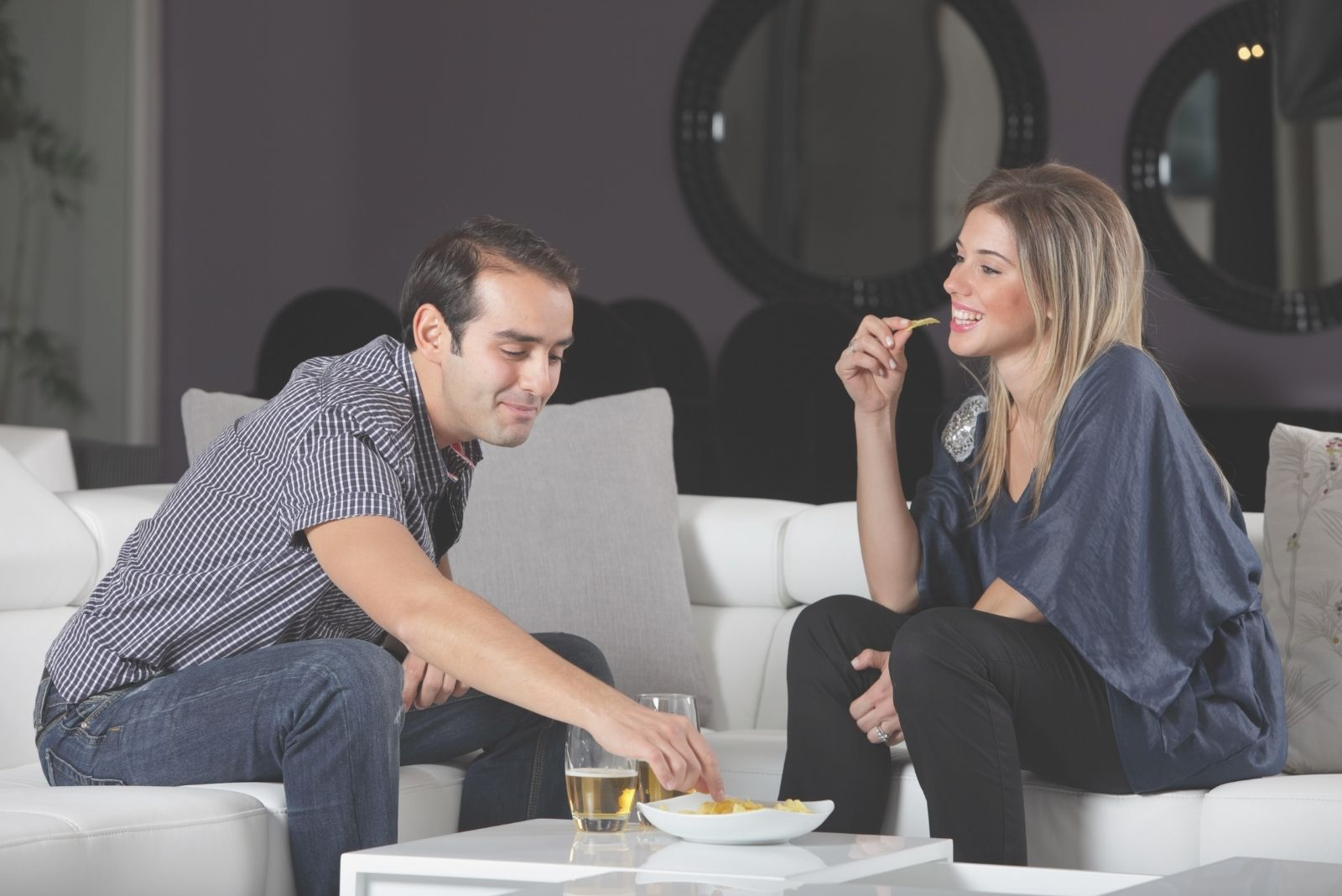 man and woman eating chips and drinking beer while sitting in a sofa