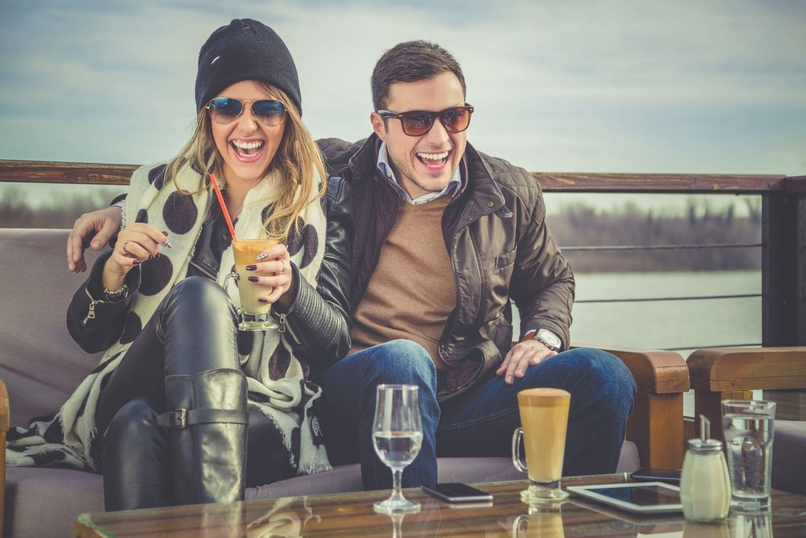 man and woman laughing wearing winter clothes sitting near the body of water and drinking beverage