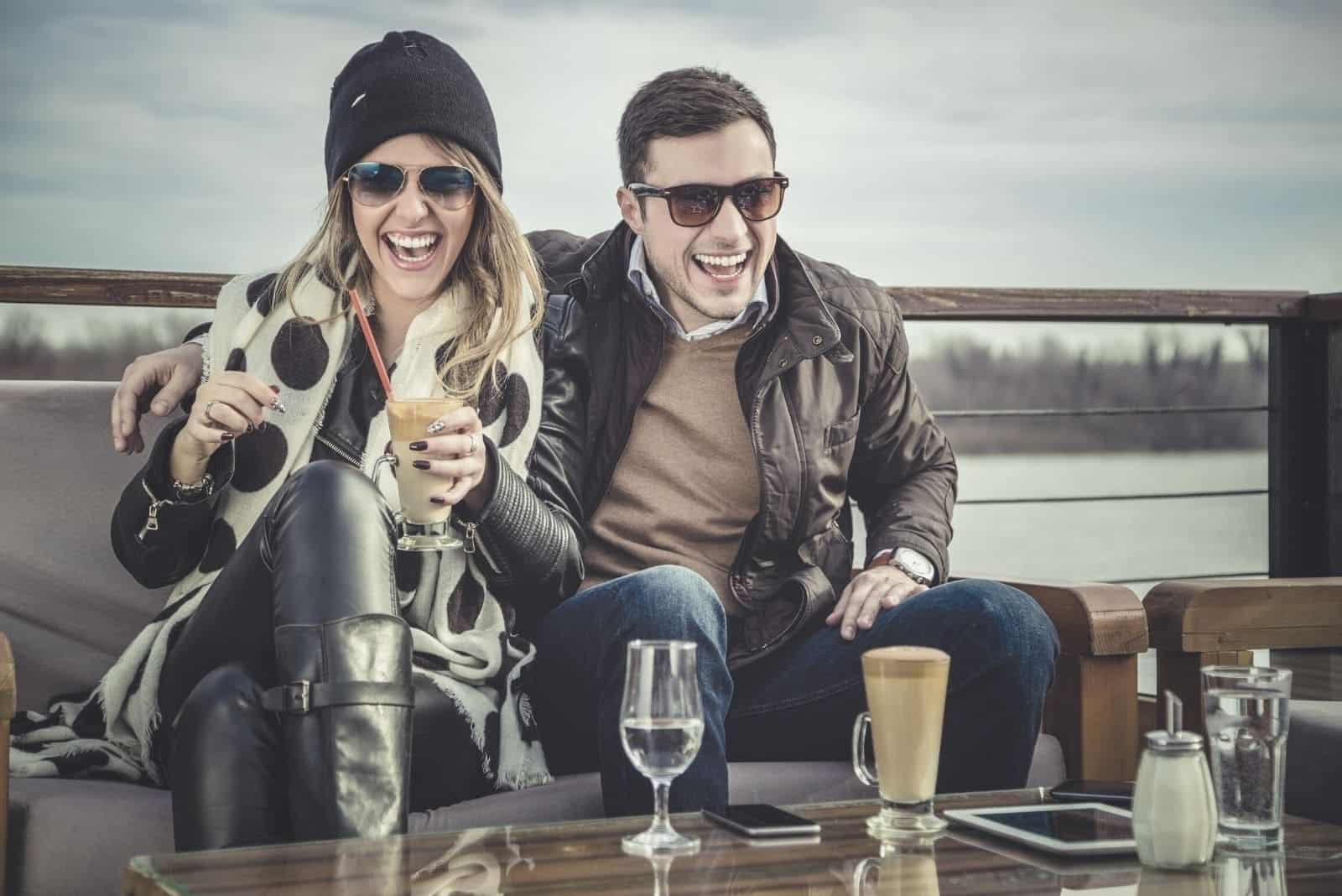 man and woman laughing while drinking with river in the background