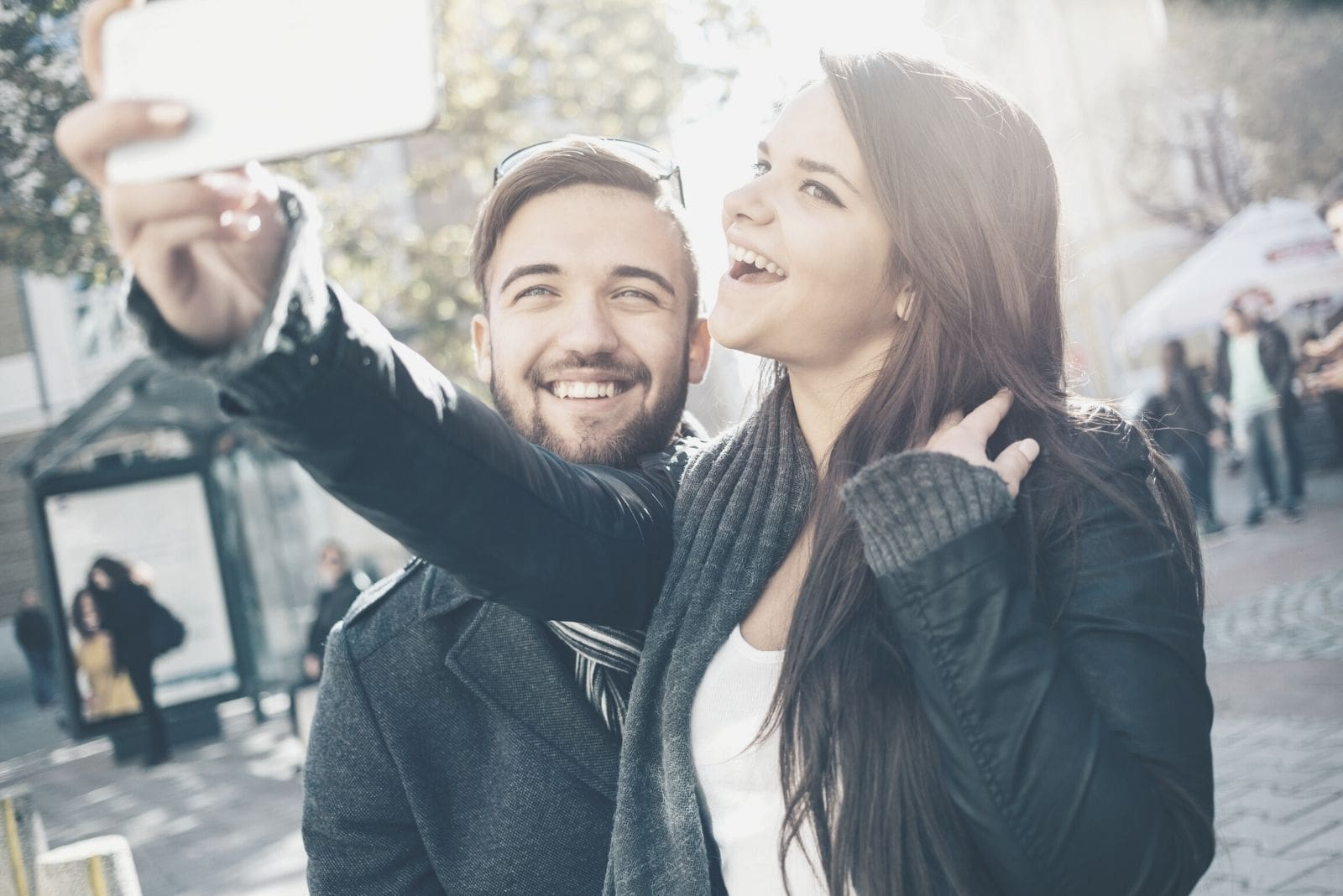 man and woman making selfie on her smartphone while walking outdoors