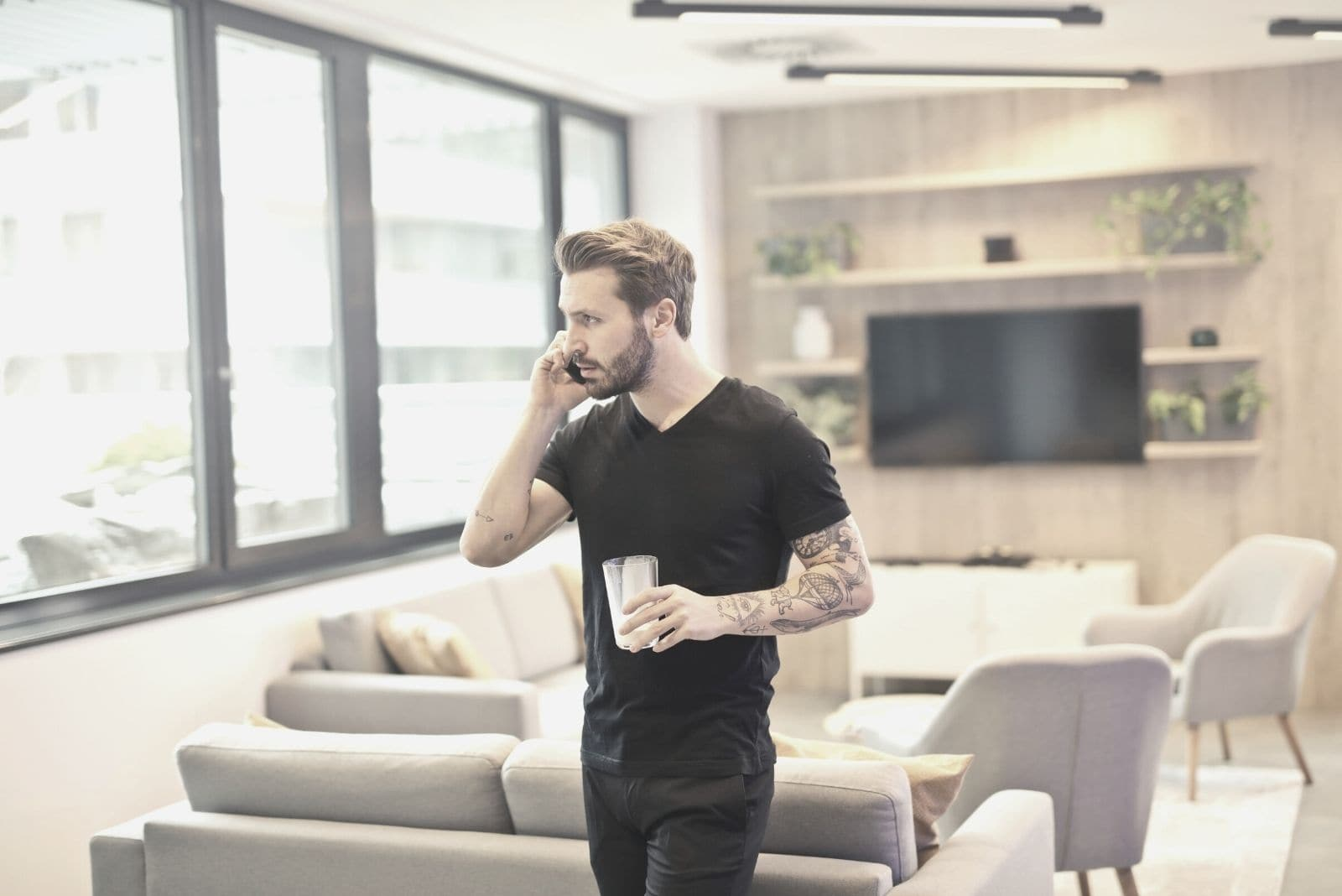 man calling on phone standing and holding glass inside the living room