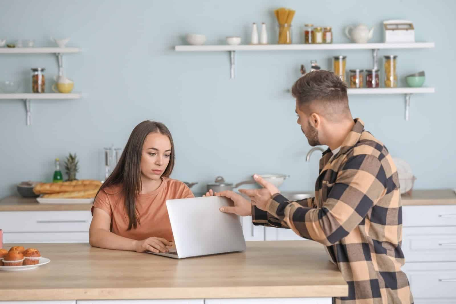 man closing woman's laptop upset while woman working on laptop in the kitchen