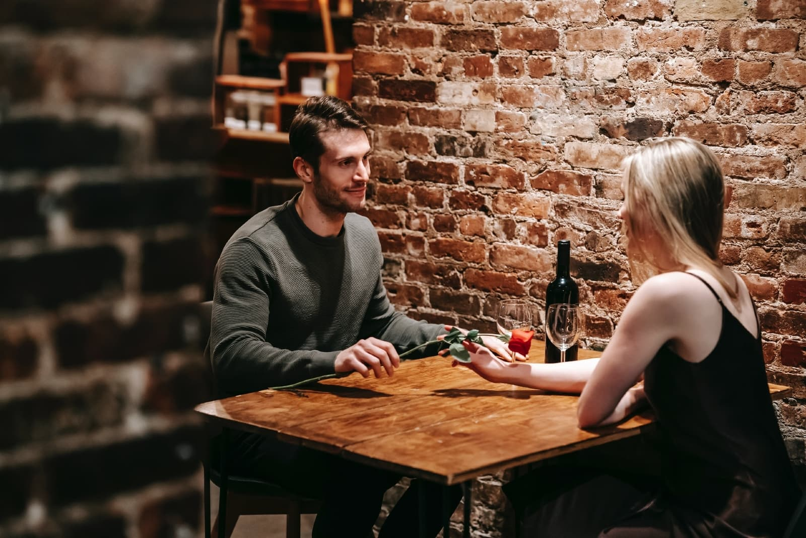 man giving rose to woman while sitting at table