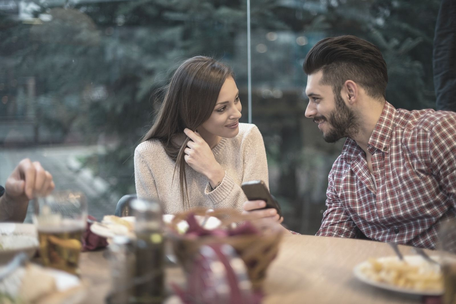 man holding a phone while sitting next to a woman in the restaurant