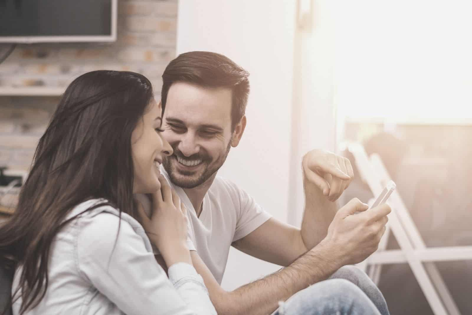 man holding a smartphone showing it a woman leaning and laughing with him sitting in the veranda