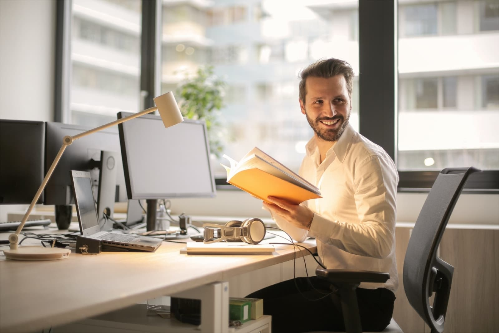 man holding book while sitting at table in office