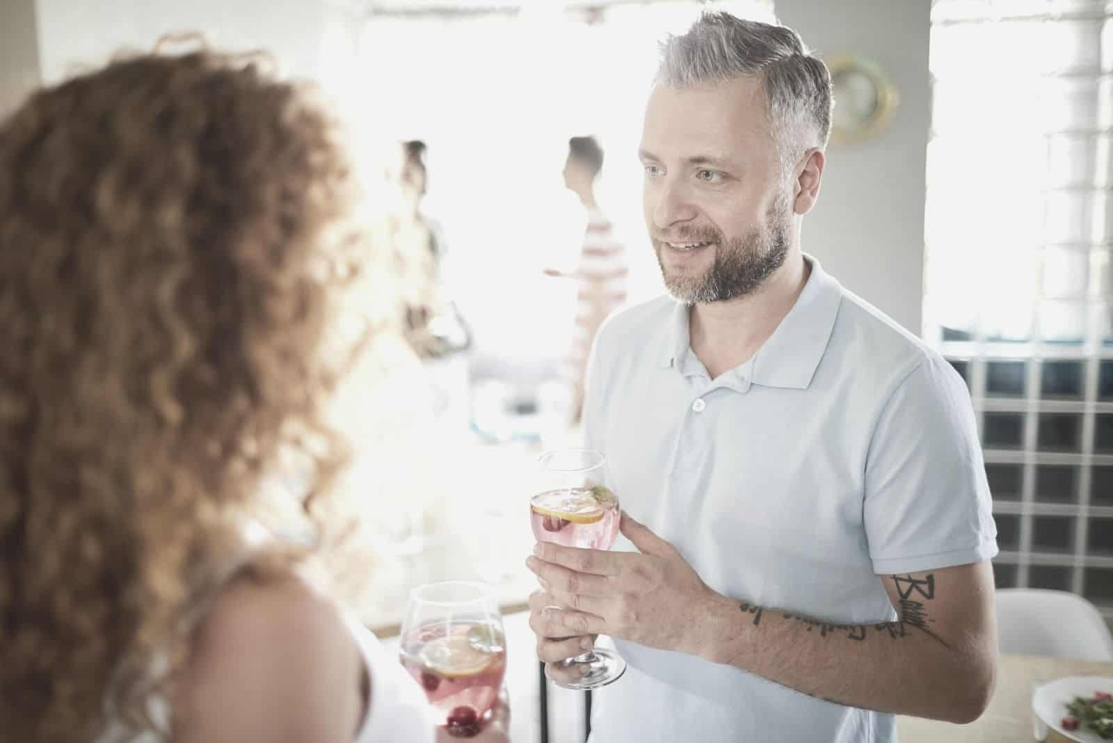 man holding wine while talking to a woman with curly hair in a get together
