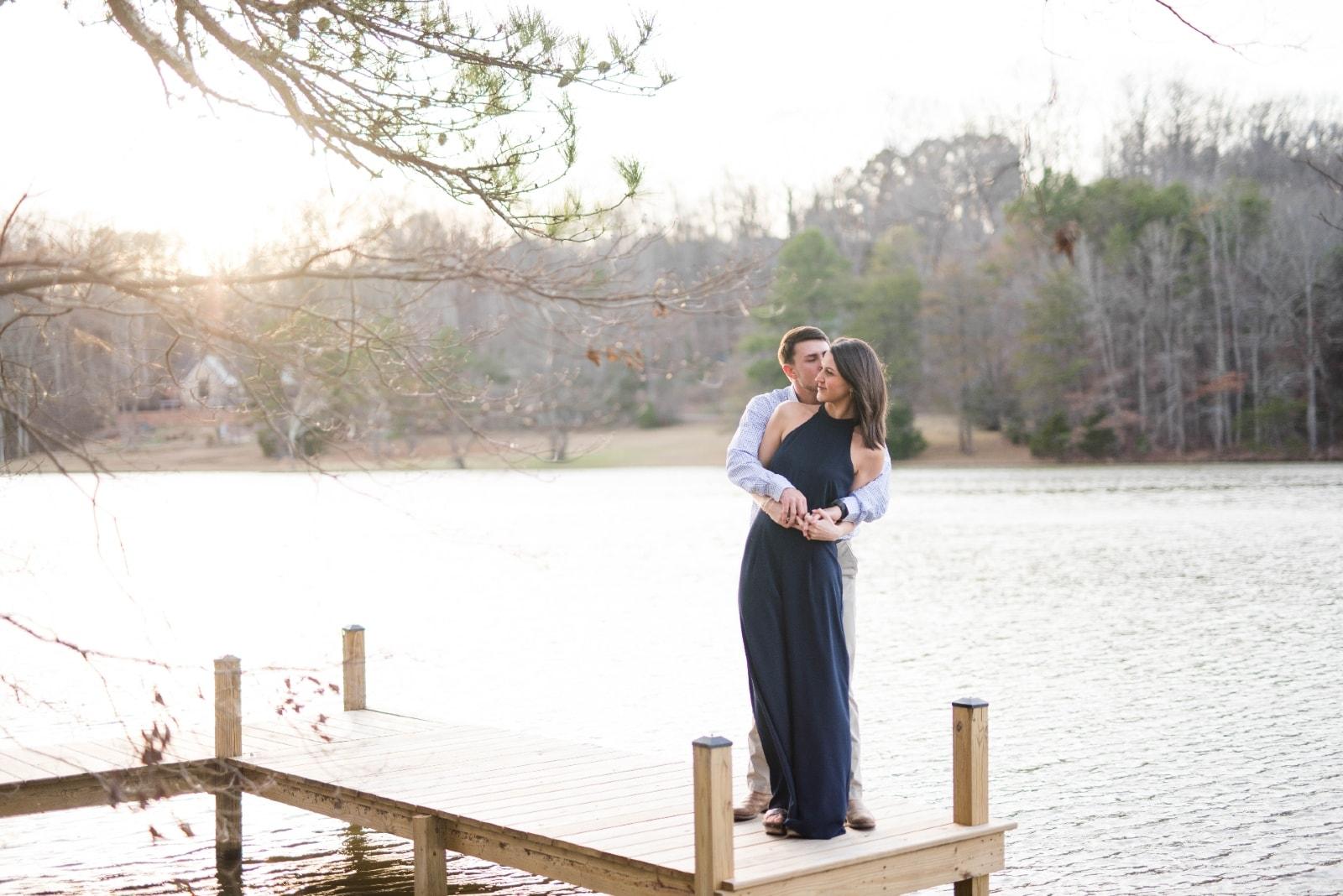 man hugging woman while standing near water