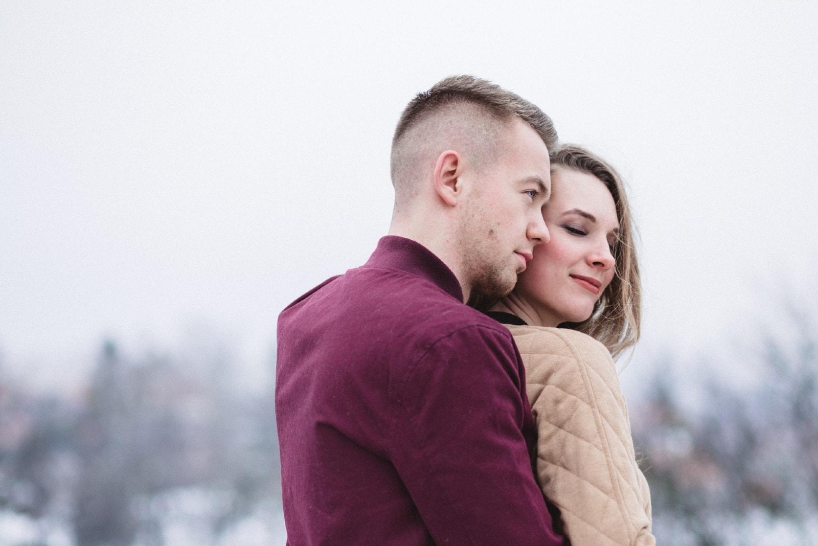 man in burgundy jacket hugging woman outdoor