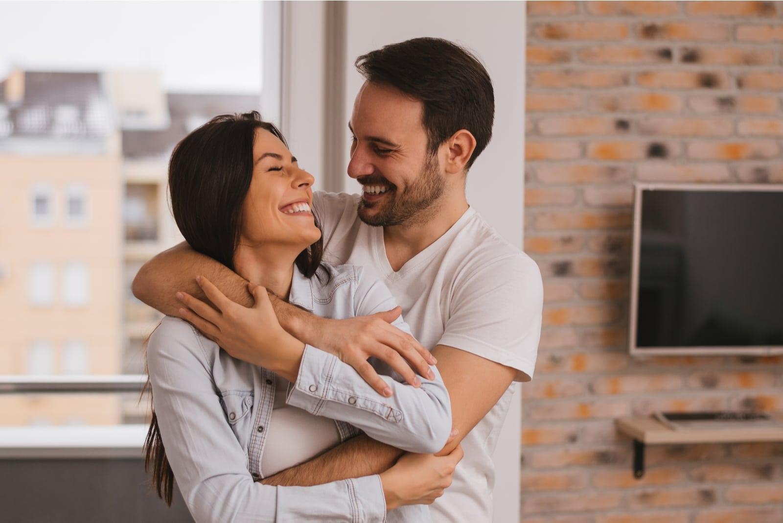 happy man hugging woman while standing indoor