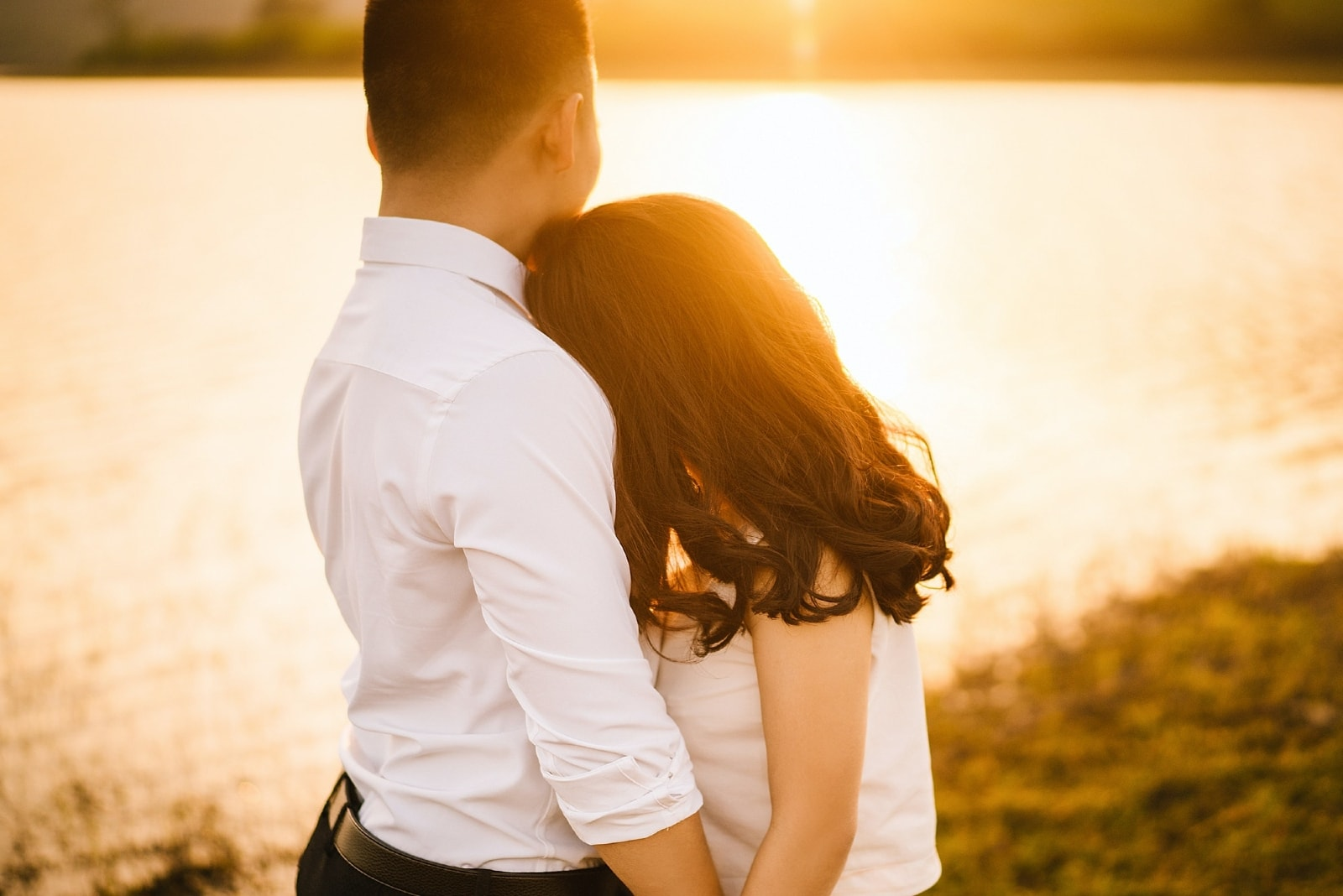 man in white shirt hugging woman while standing near water