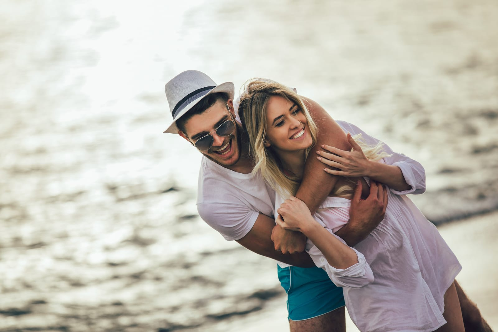 man hugs woman from back by the sea