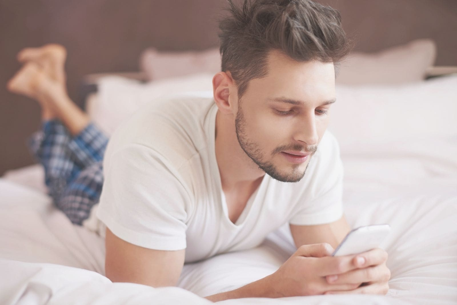 man in bed texting lying with elbows supporting the body wearing pajamas