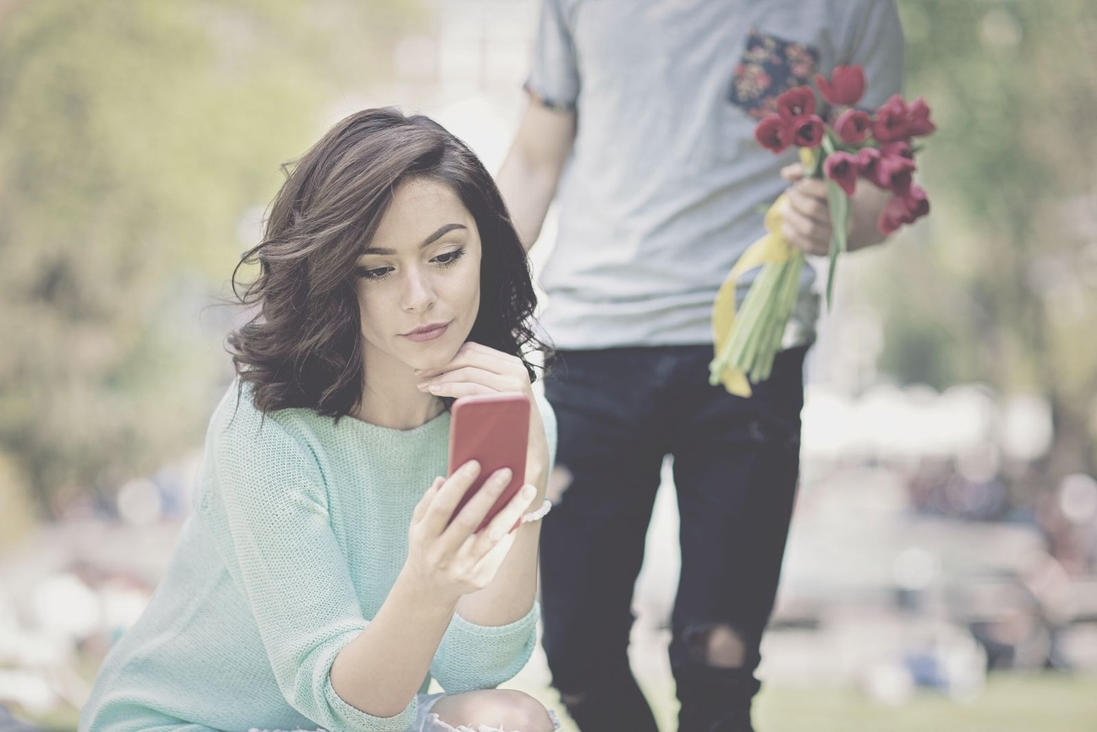 man is bringing flowers to a woman sitting in the park looking at her smartphone