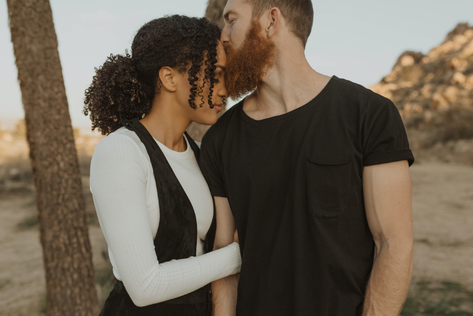 man kissing woman's forehead while standing near tree