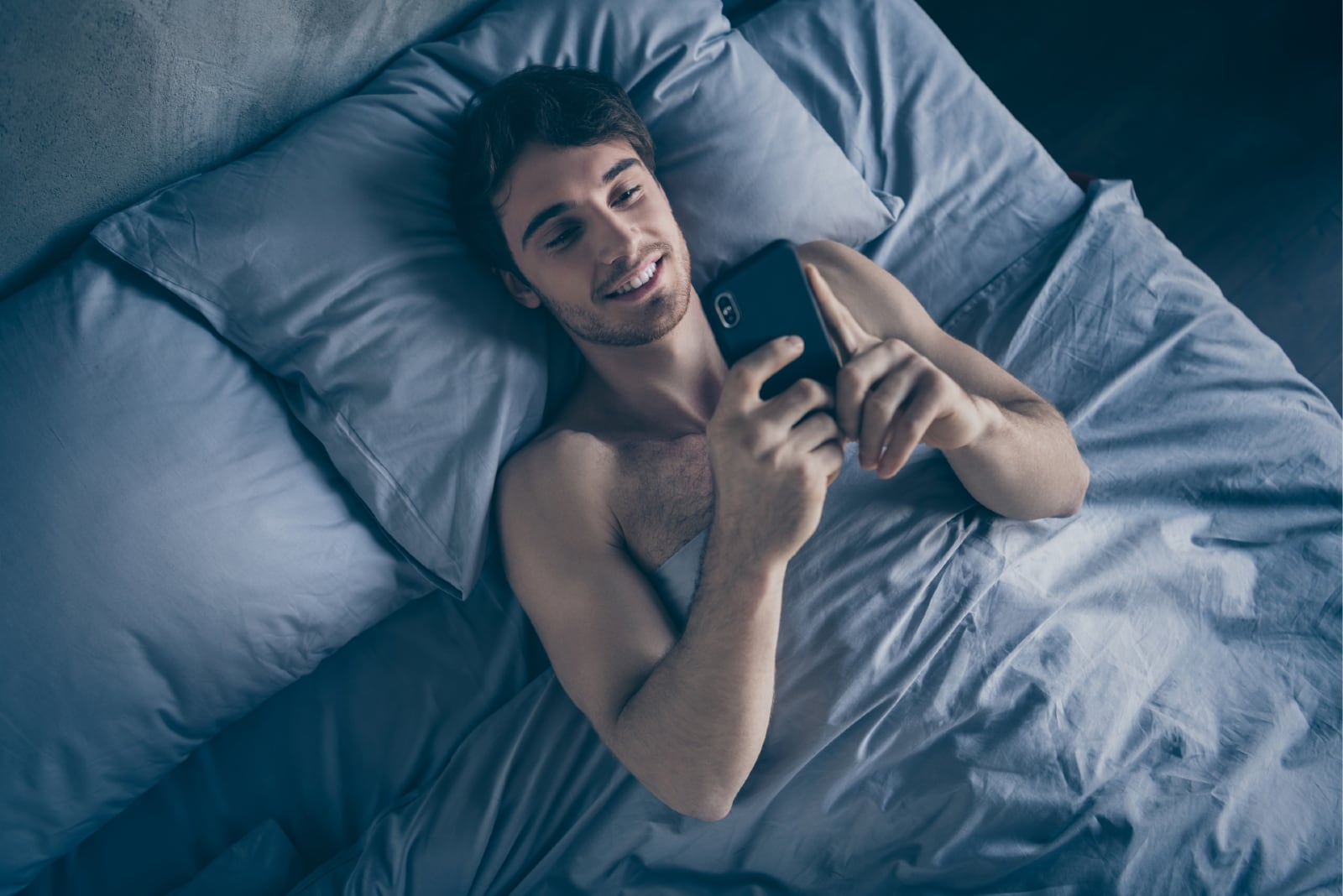happy man laying on bed while using smartphone