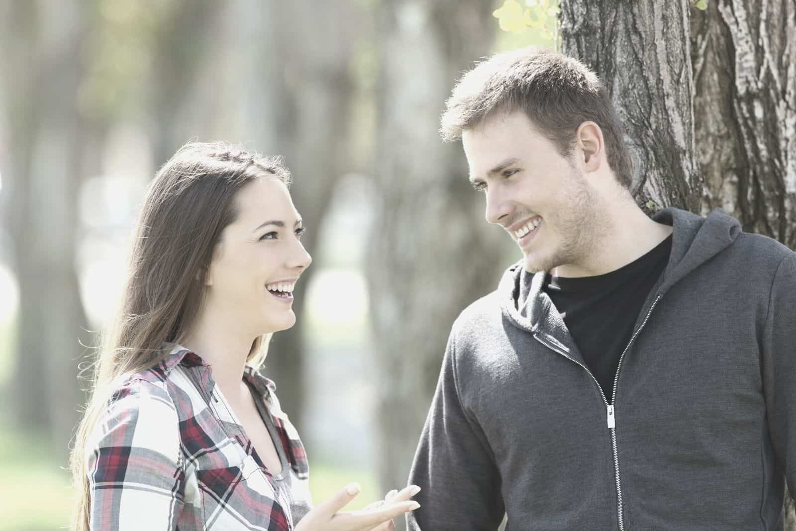 man leaning on the tree talking and laughing with a beautiful woman