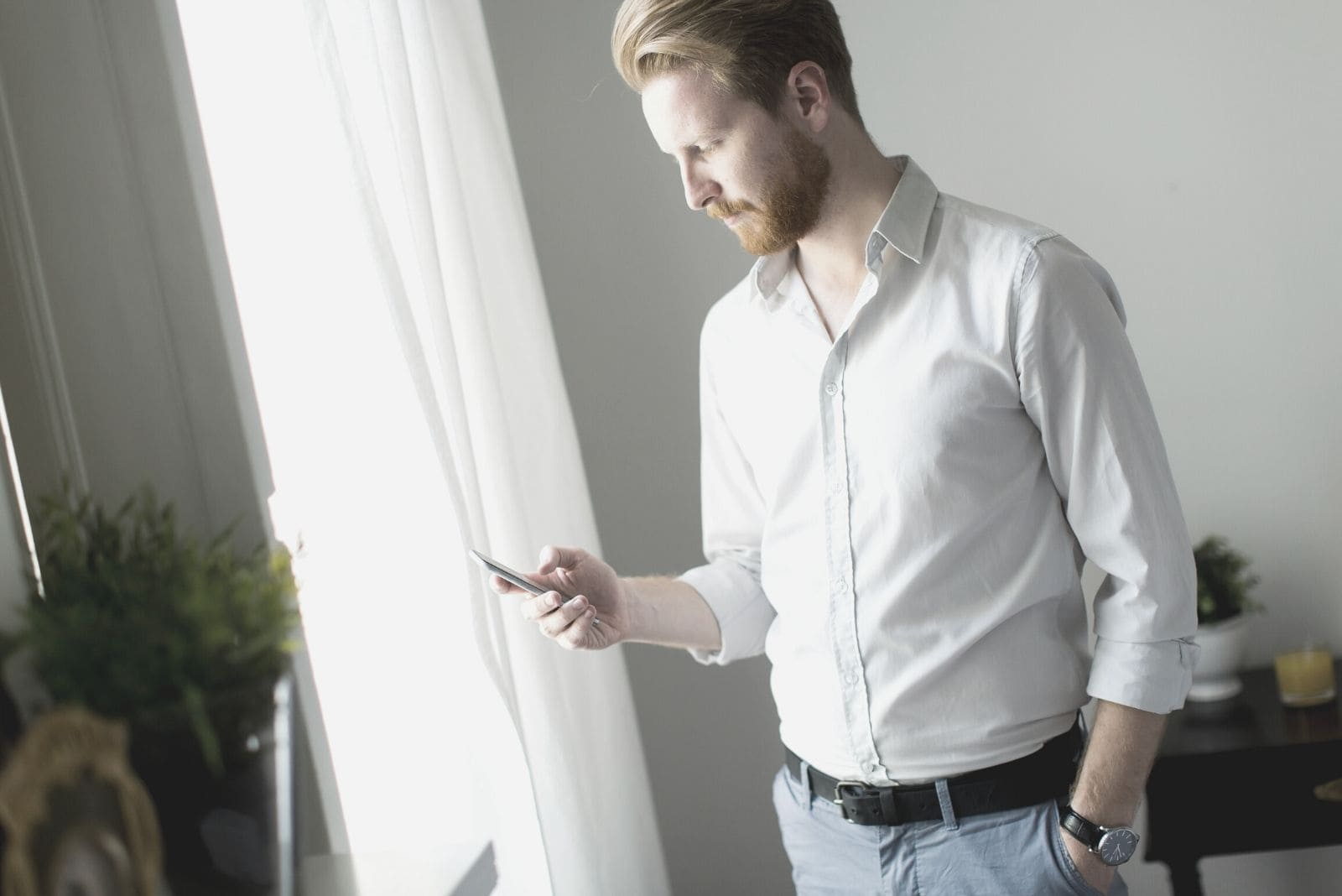 man looking at his phone with one hand on his pocket while standing inside a room