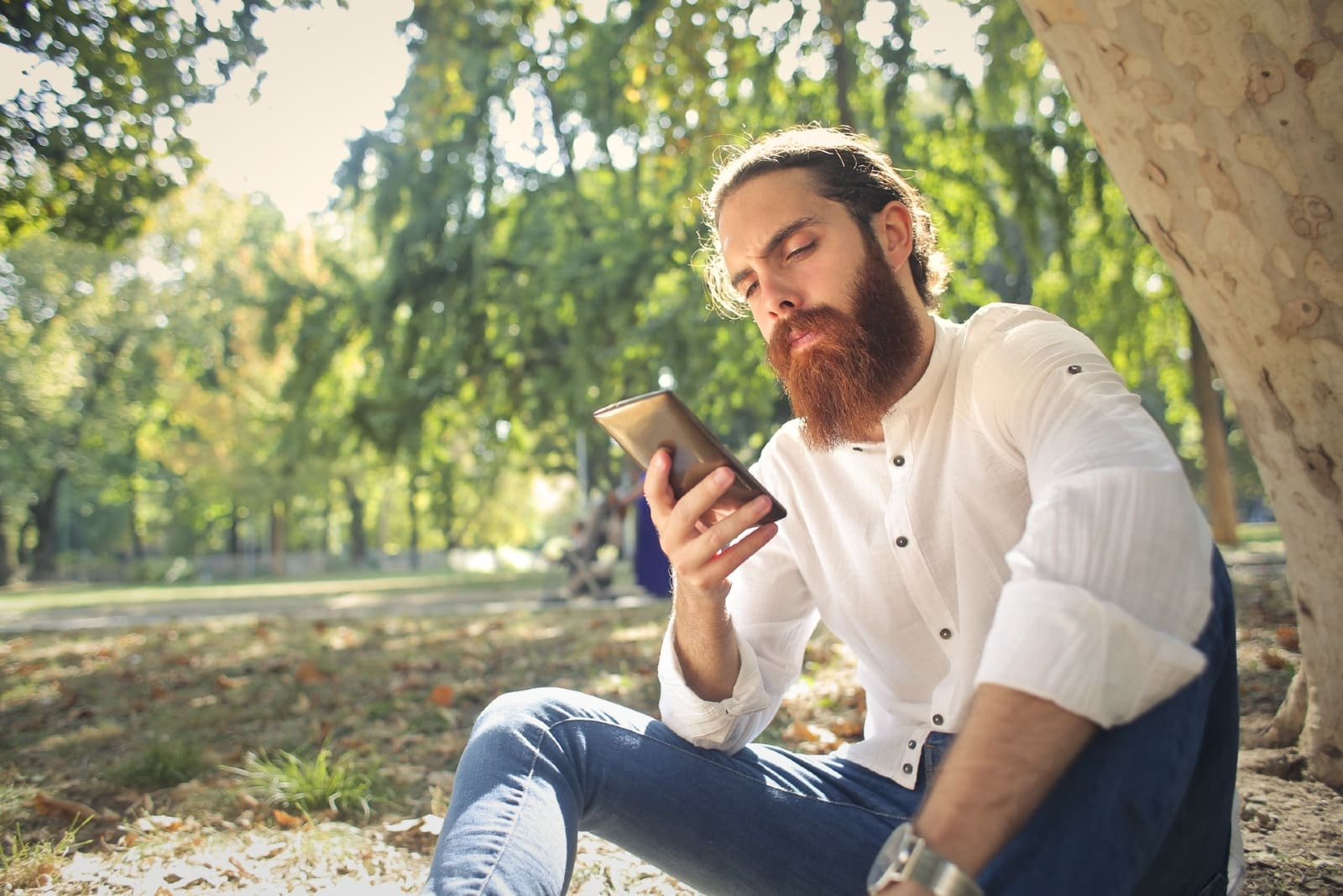 man with beard looking at phone while sitting near tree
