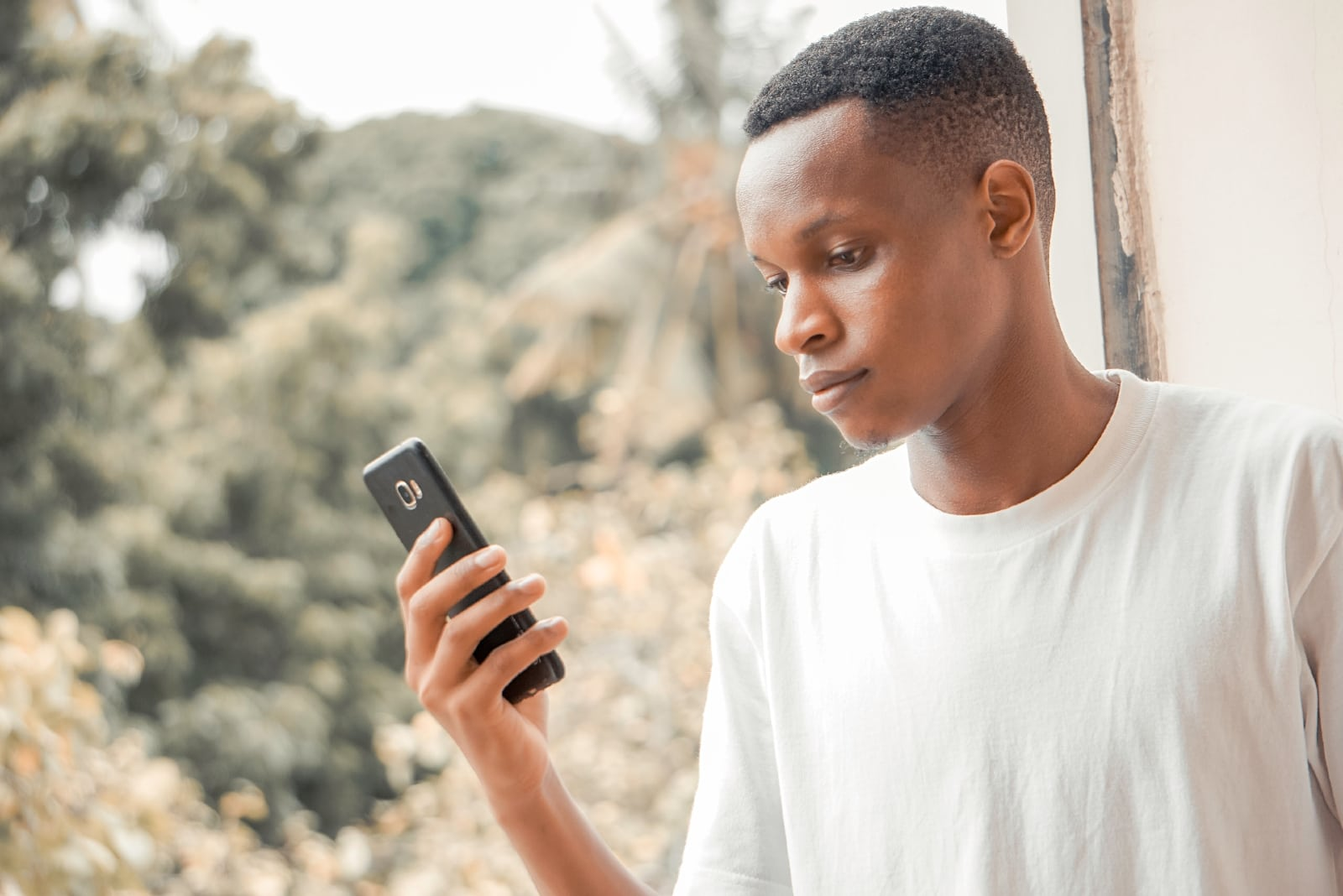 man in white shirt looking at phone outdoor