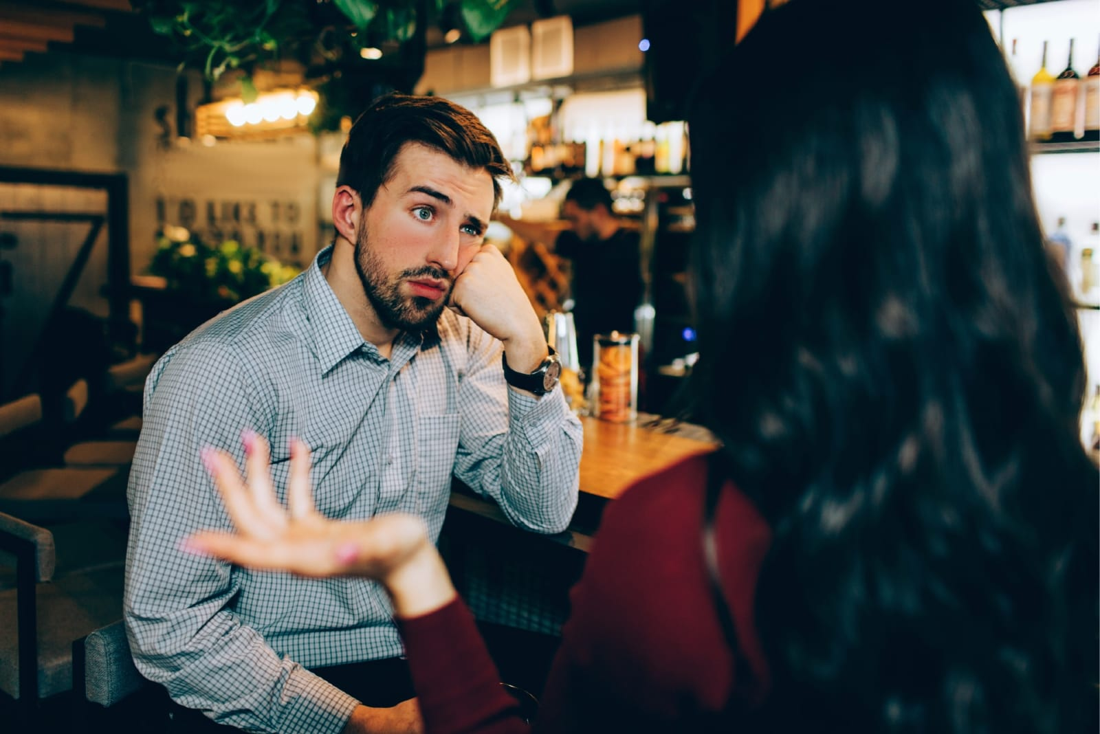 bored man looking at woman while sitting in bar