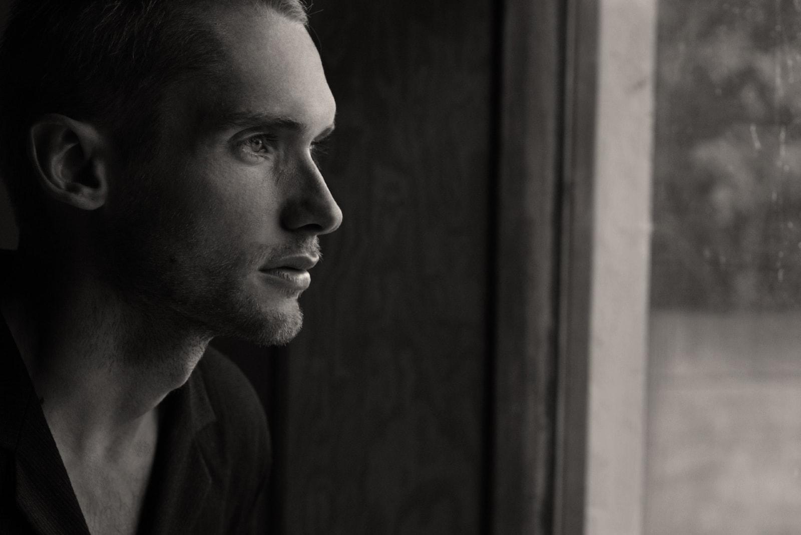 pensive man in black shirt looking through window