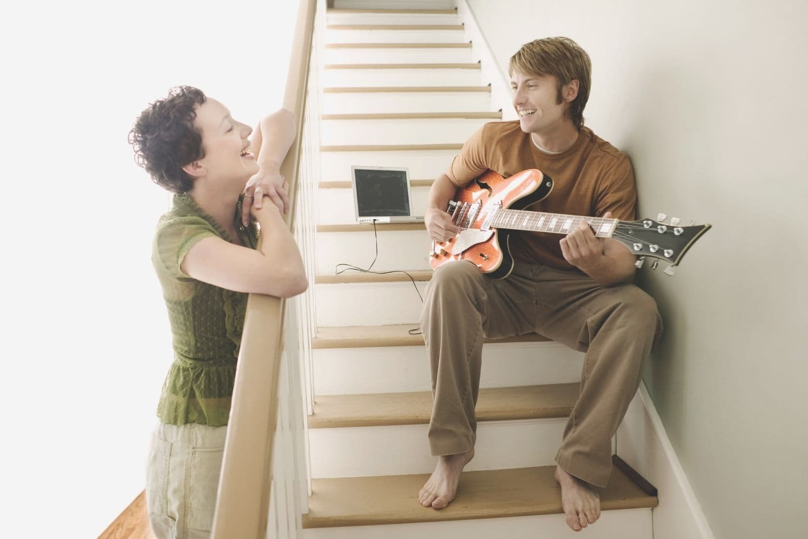 man playing guitar and sitting in the stairs while talking to the woman laughing