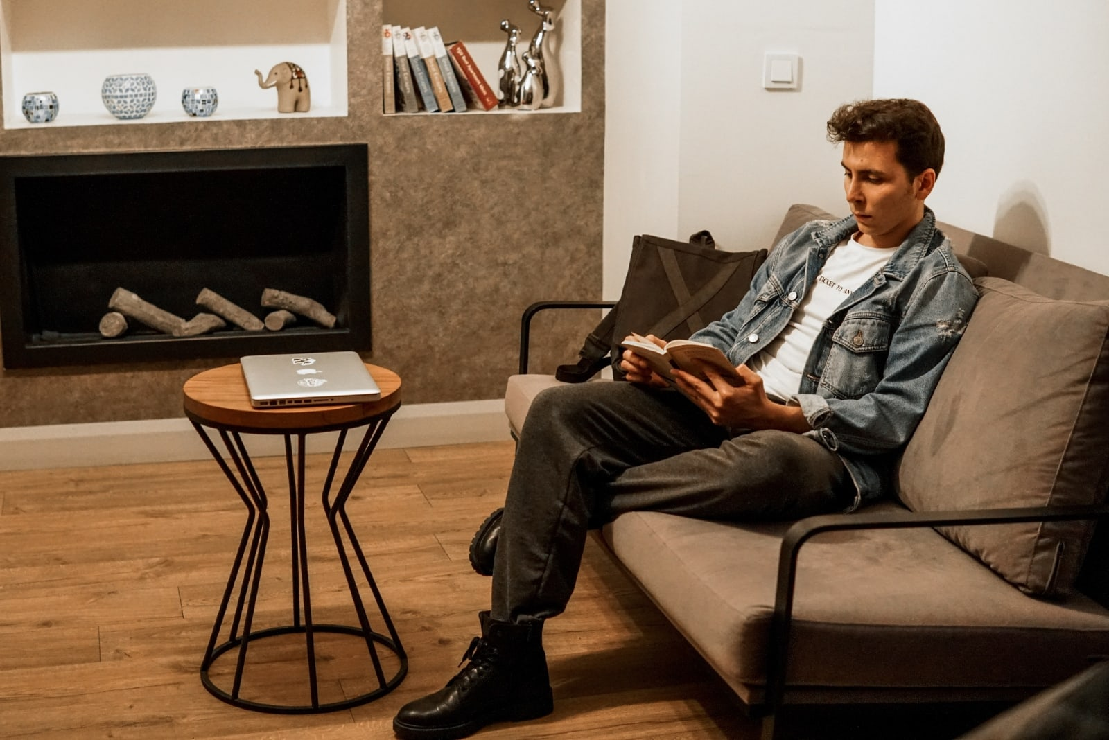 man reading book while sitting on sofa