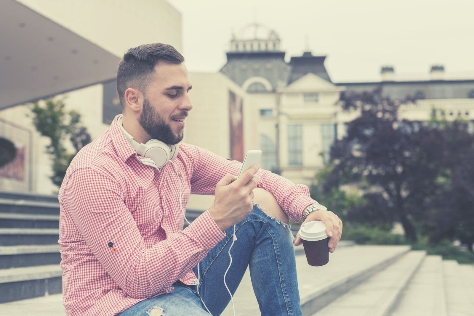 man sitting in public stairs of the plaza drinking coffee and texting with a headphone around his neck