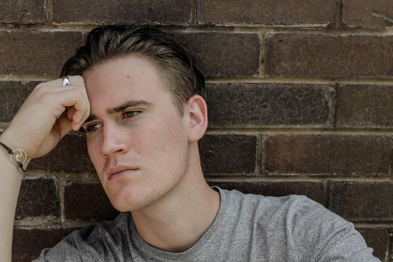 sad man in gray shirt sitting near wall