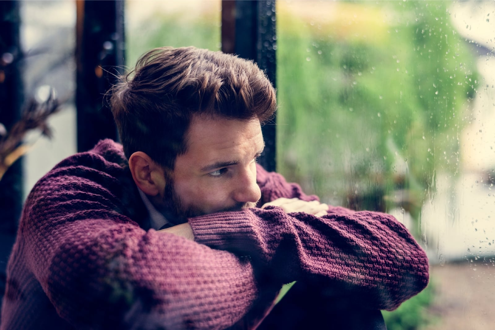 sad man in burgundy sweater sitting near window