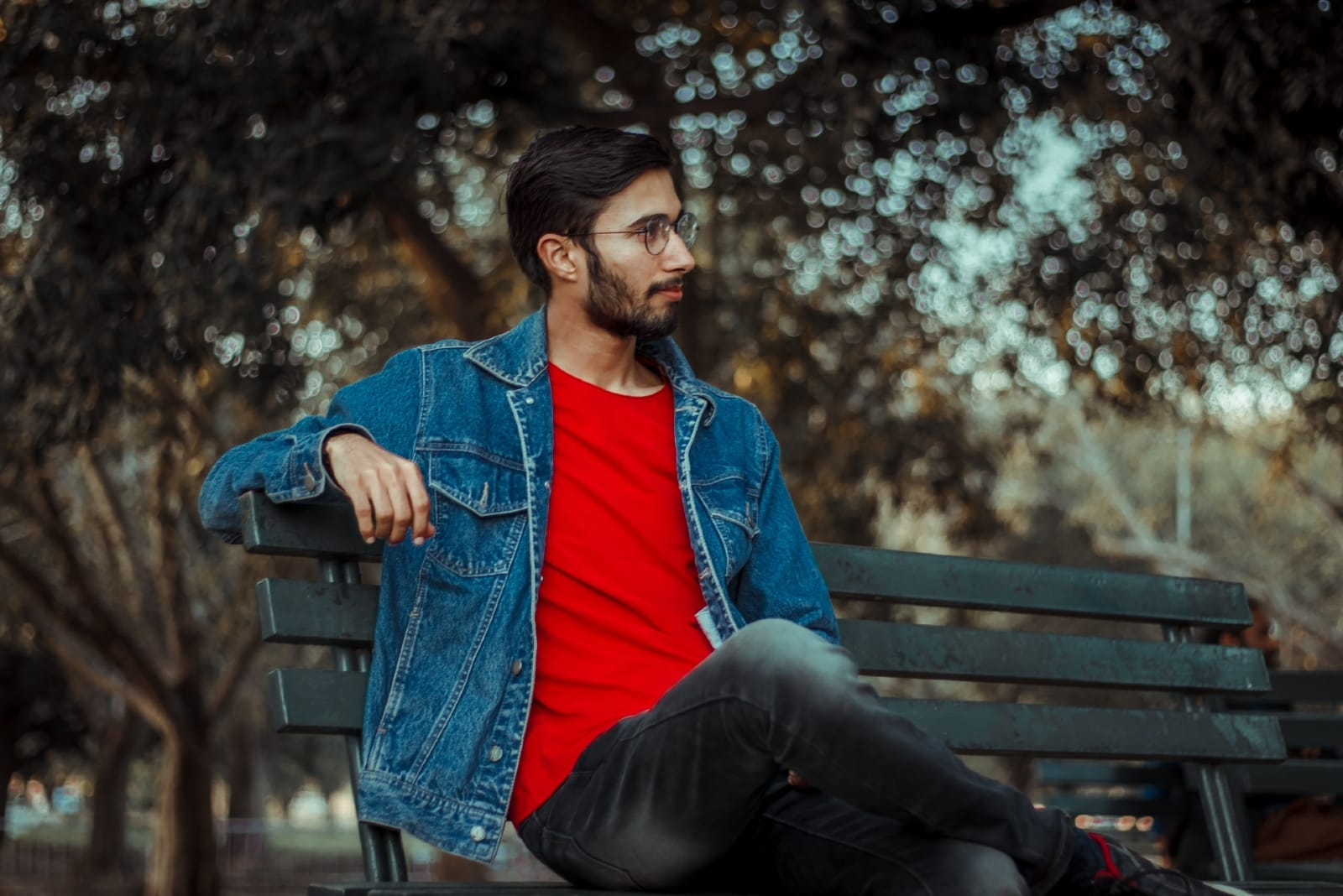 man in denim jacket sitting on bench