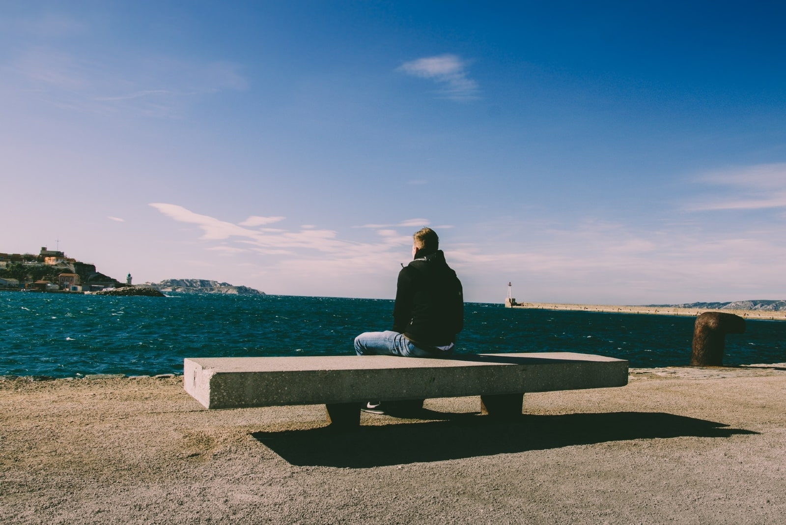 man sitting on bench while looking at sea