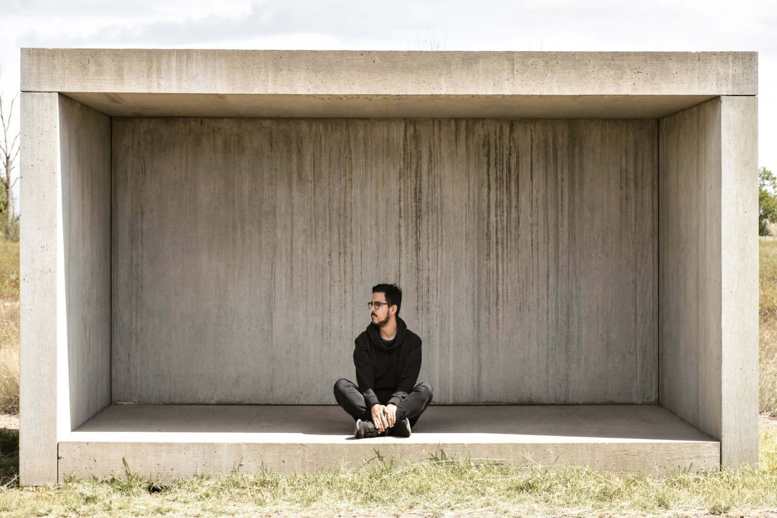 man in black hoodie sitting on concrete surface