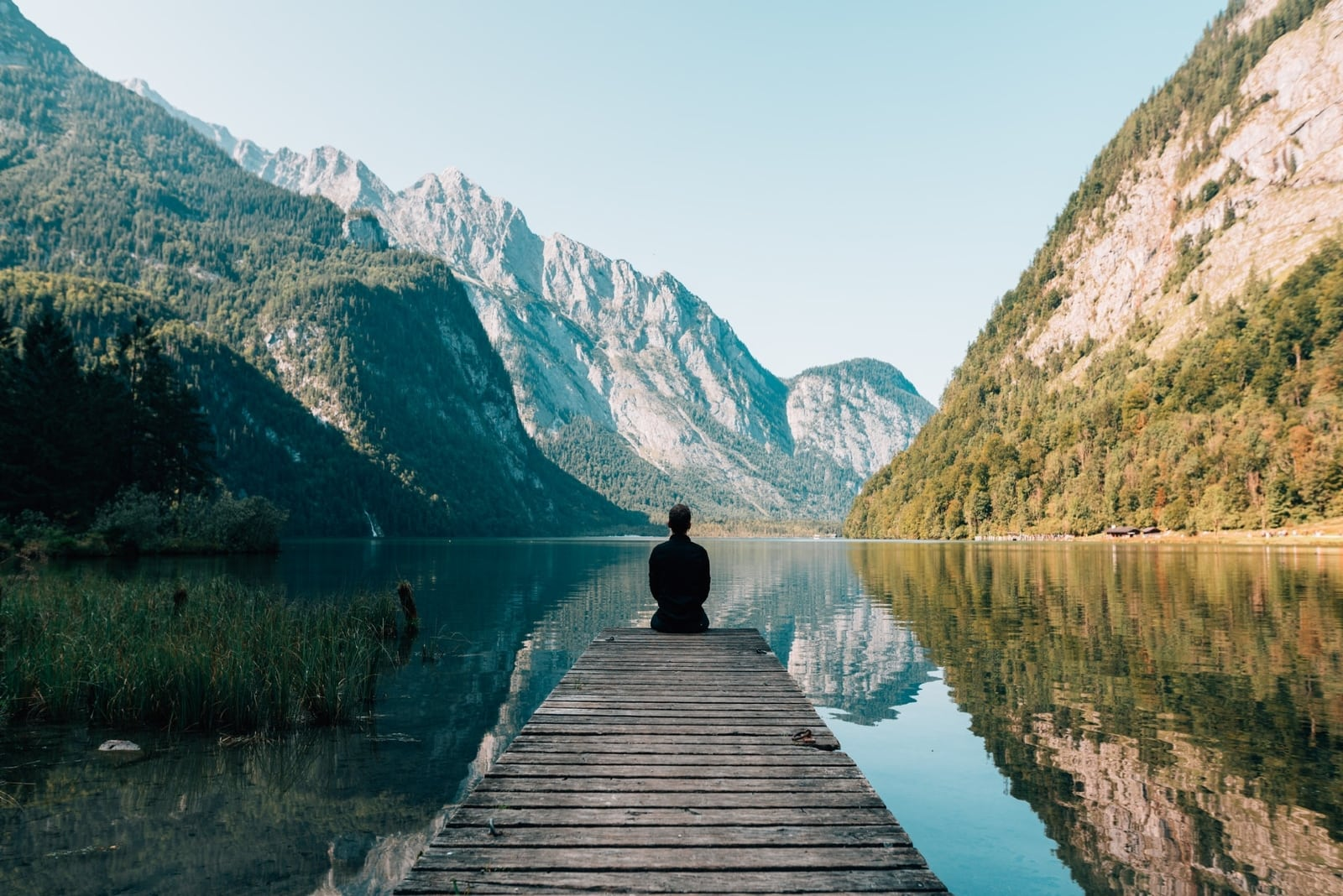 man sitting on dock looking at water