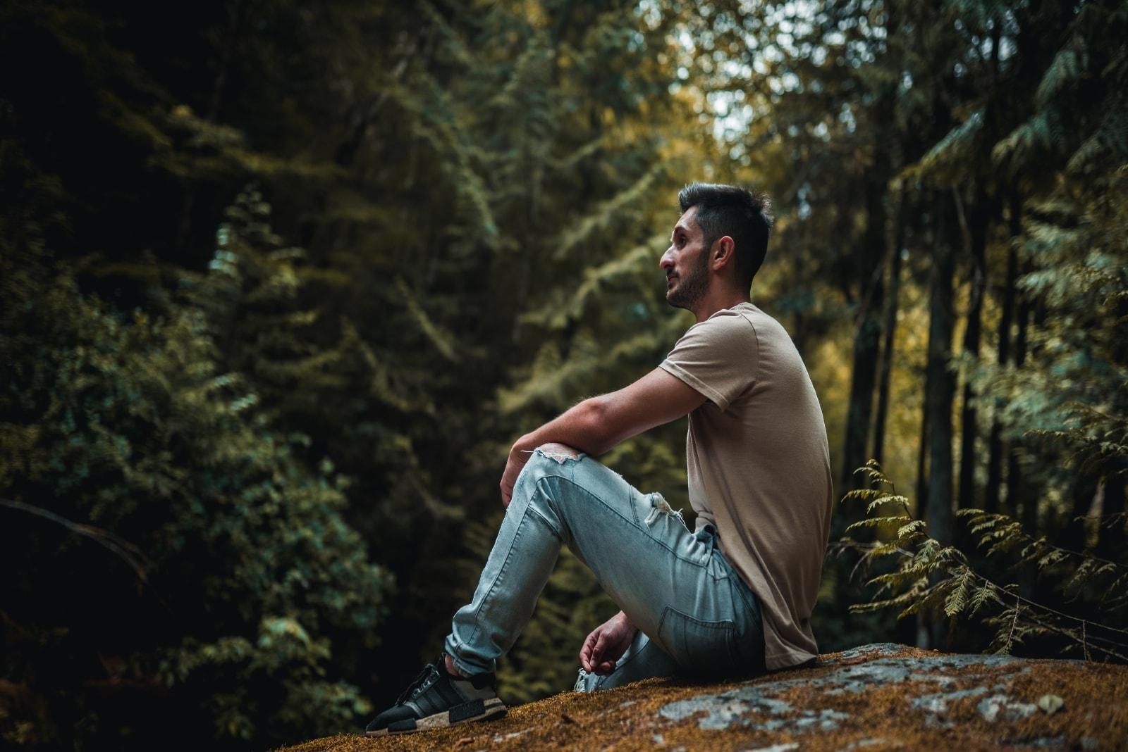 man sitting on ground near trees