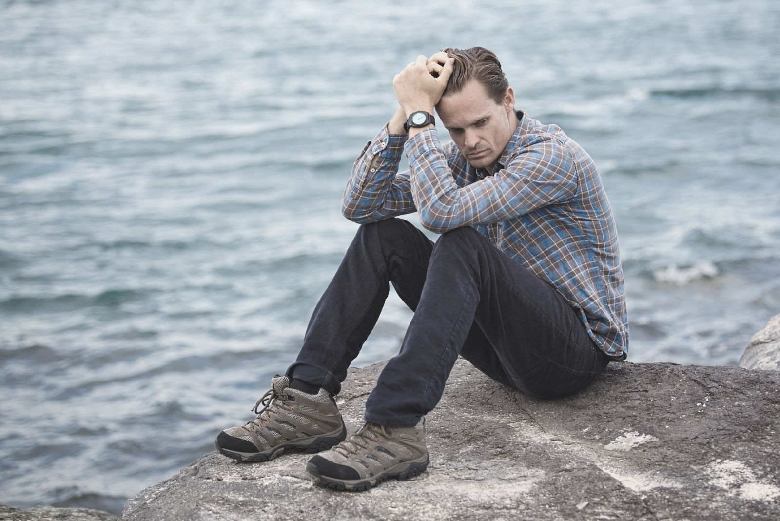 man sitting on the rock near the body of water wearing blue and maroon plaid shirt