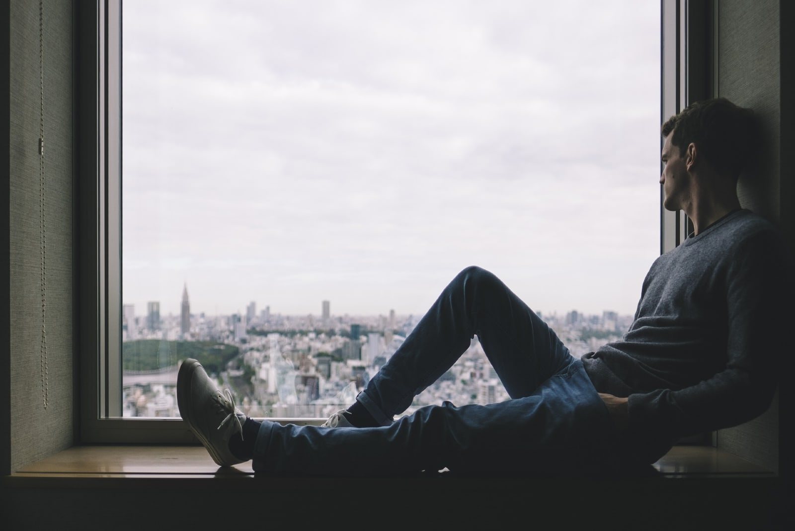 man sitting on window pane looking at city