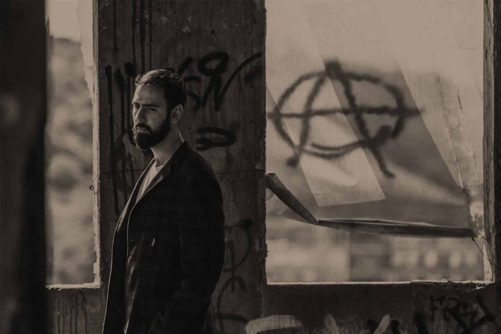 sad man with beard standing near wall