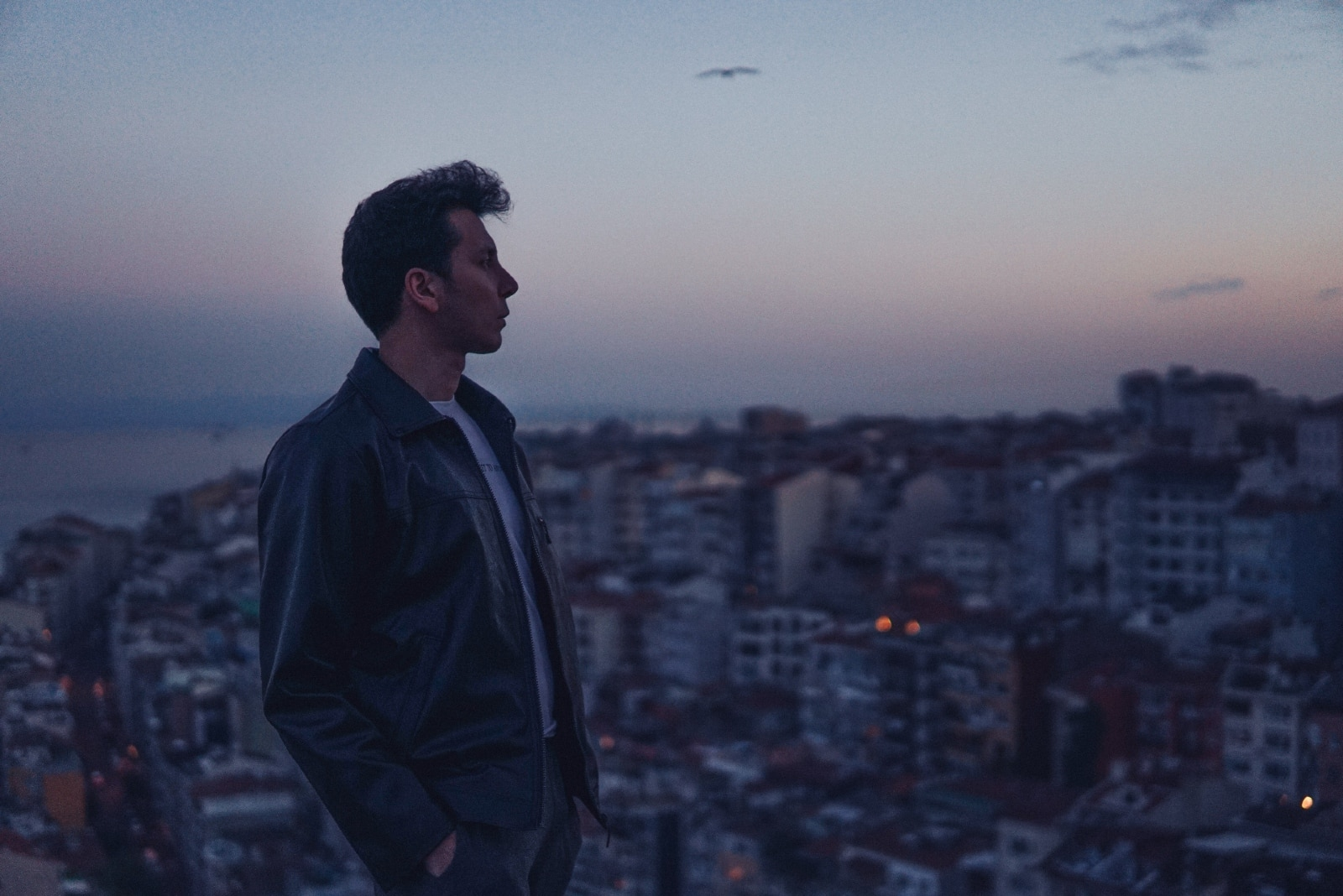 man in black jacket standing on rooftop during sunset