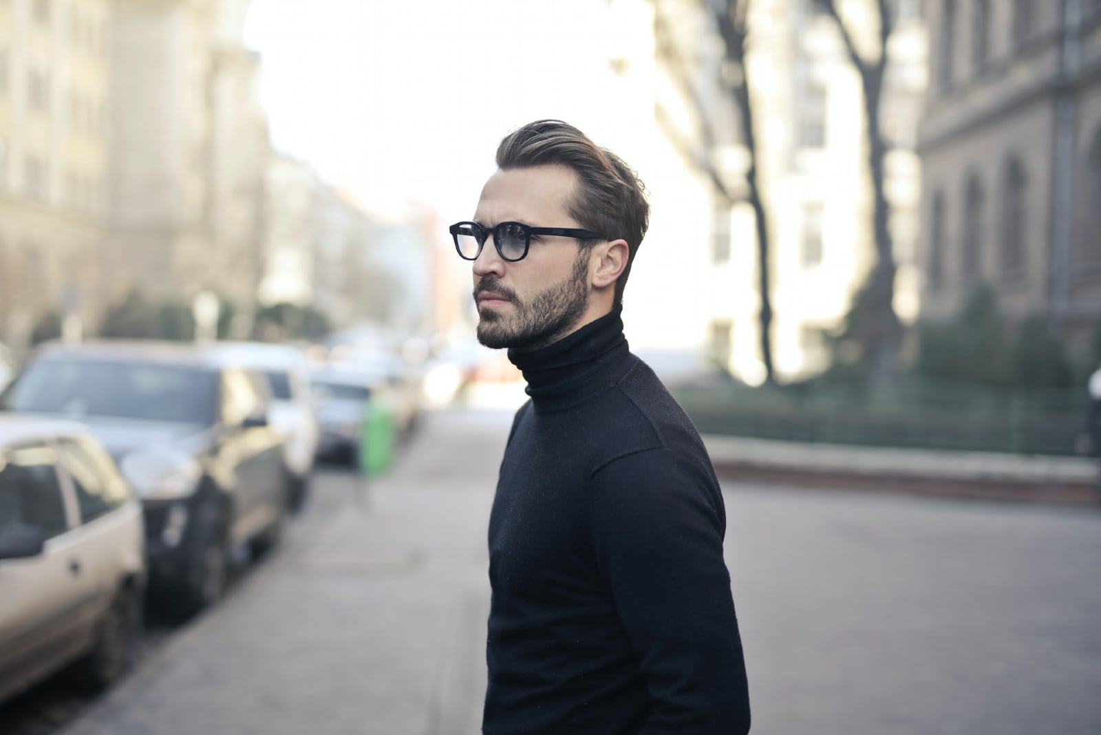 man in black turtleneck shirt standing on the street
