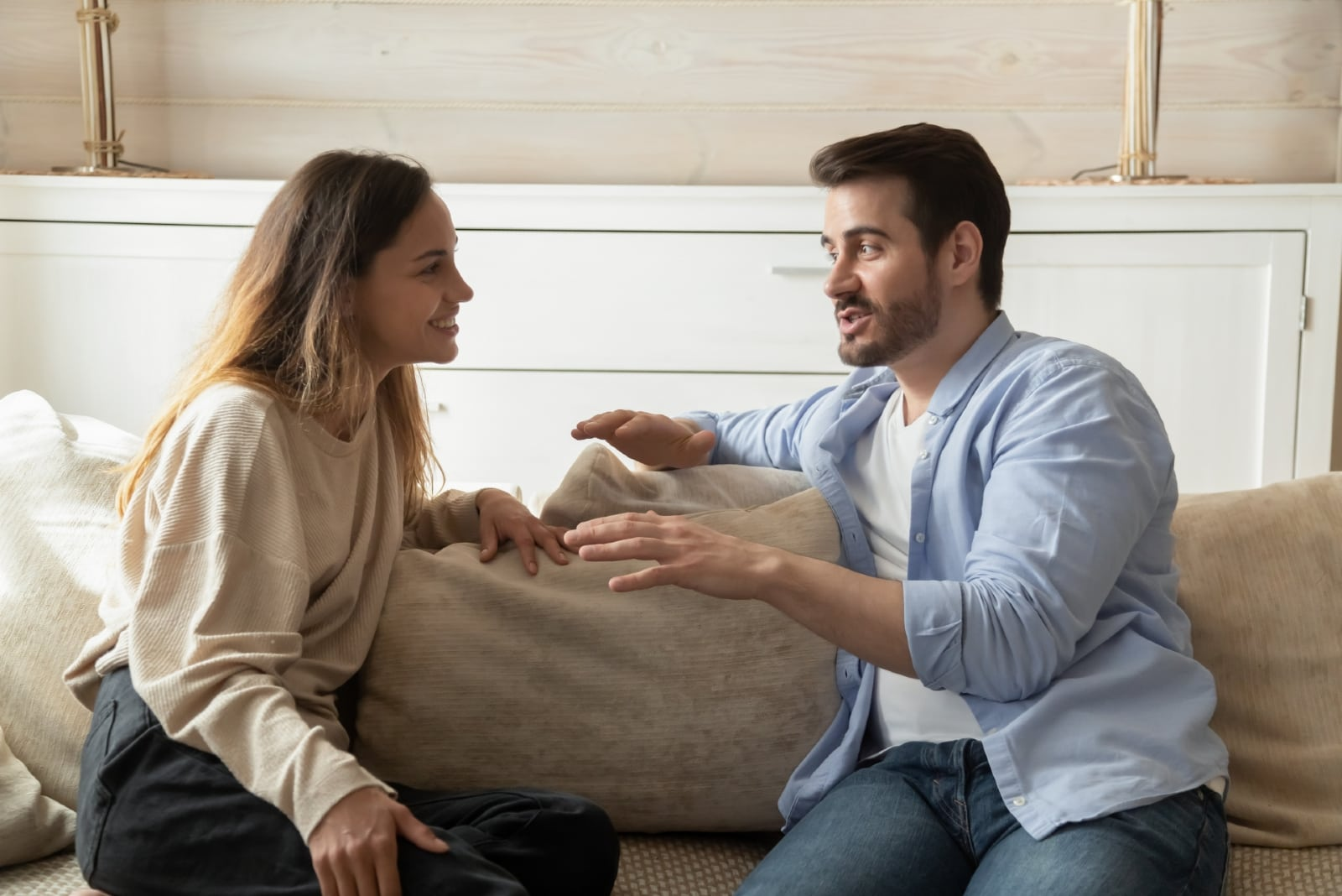 man talking to woman while sitting on sofa