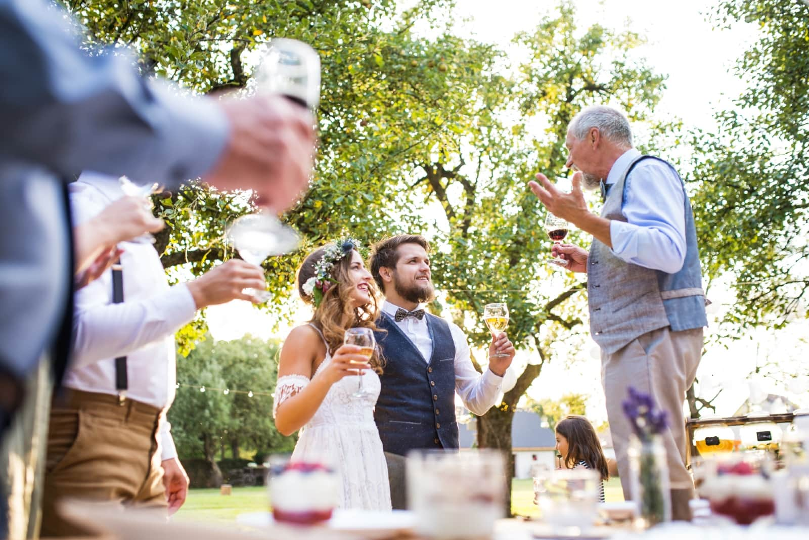 man talking to groom and bride while holding wine glass