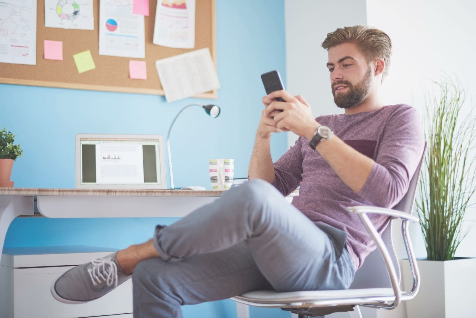 man texting in his mobile phone while sitting inside office