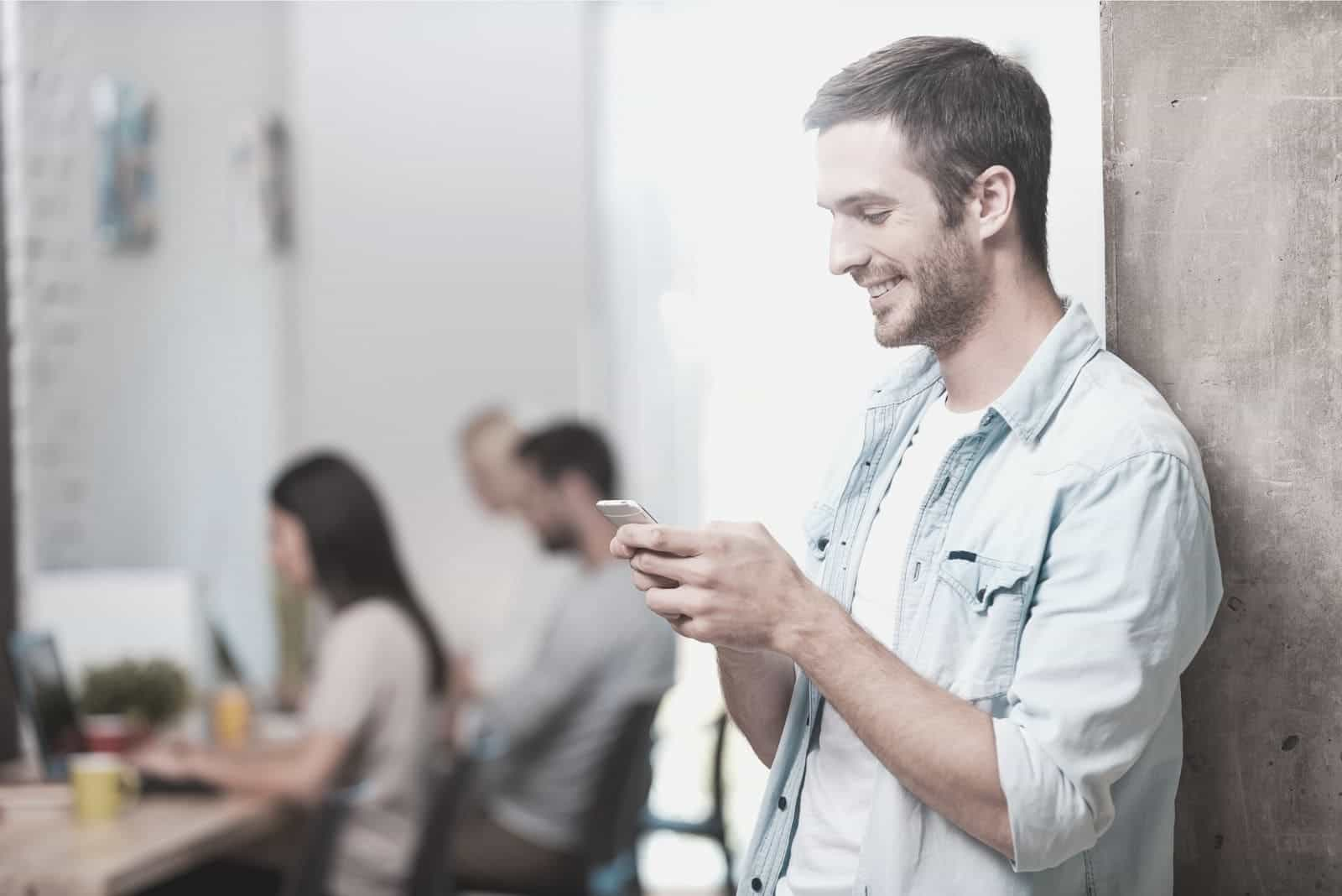 man texting inside the office with colleagues busy working in the table