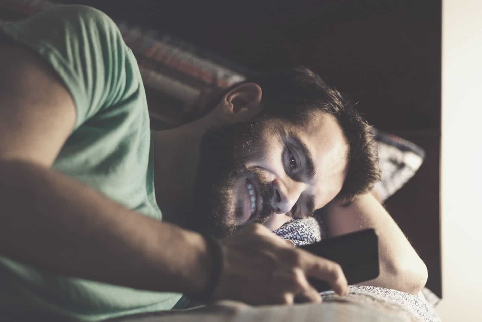 man texting while lying down in bed smiling and in dark room