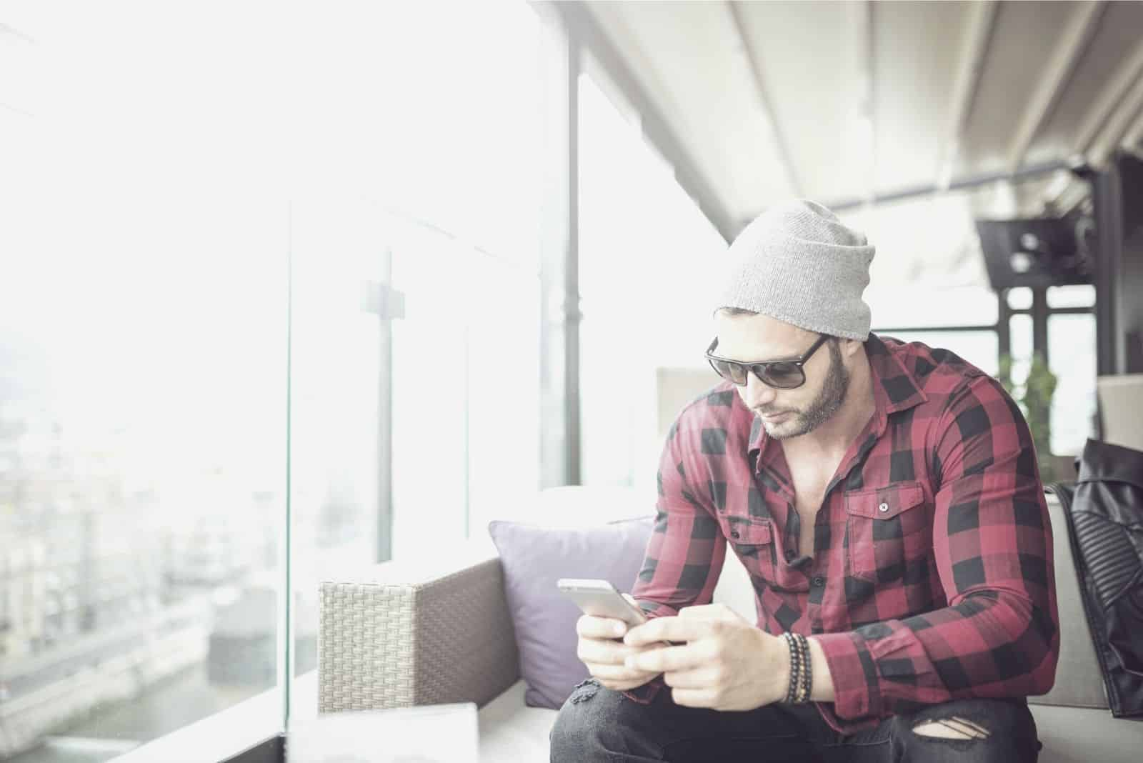 man texting while sitting inside the cafe wearing bonnet and sunglasses