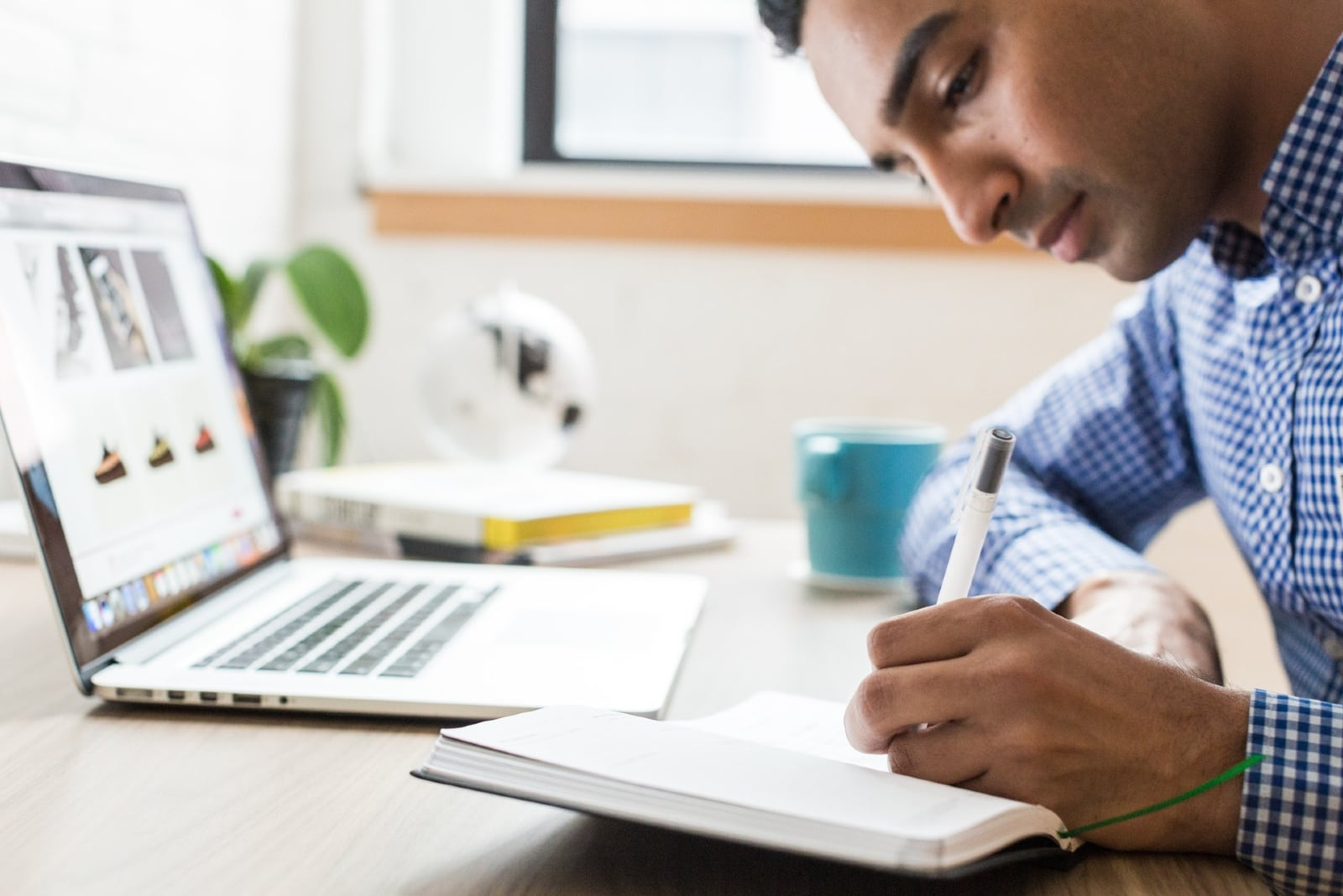 man using pen while sitting at table in office