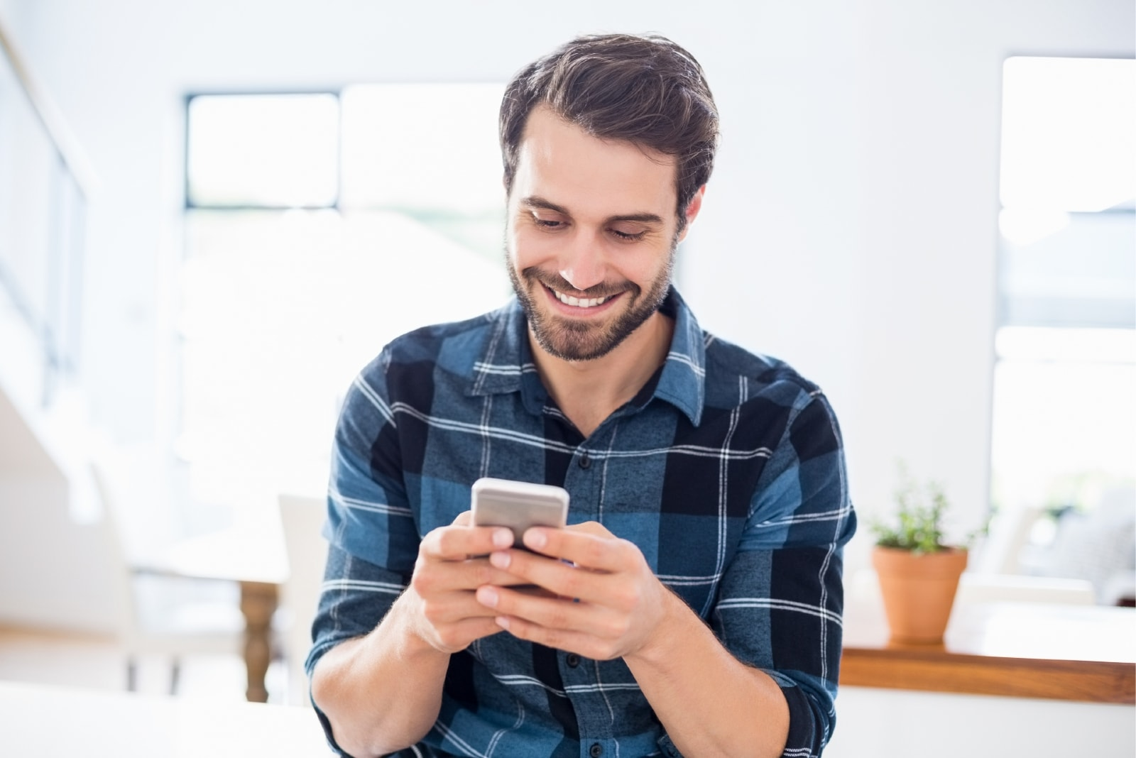 happy man in blue checked shirt using phone indoor