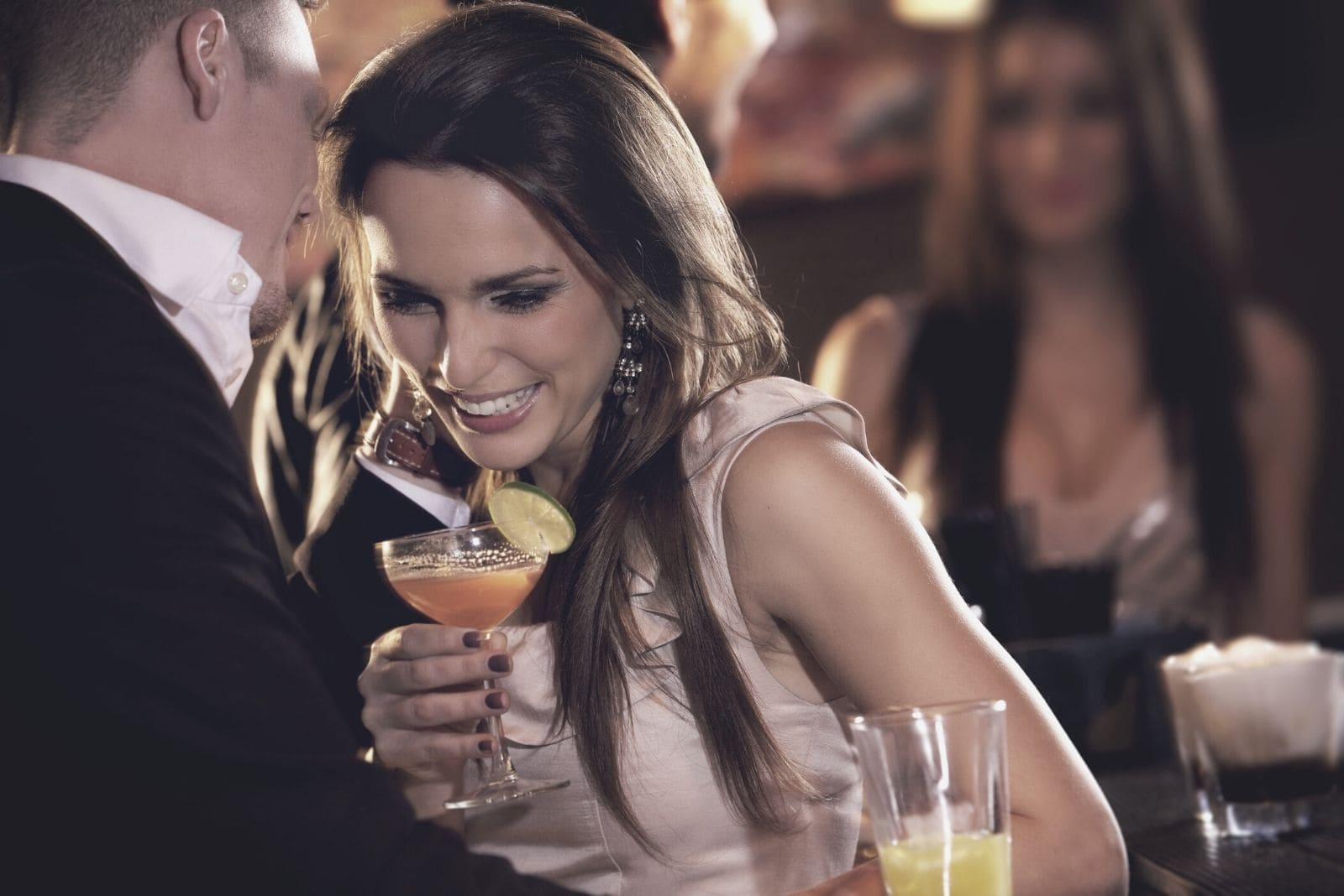 man whispers on woman in a party/club while drinking wine
